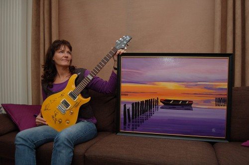 Anna Schat-Vanger with her painting and the guitar she won
